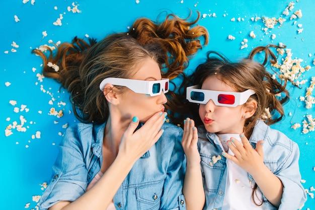 Bekijk above verbazingwekkende vrolijke meisje tot met moeder in popcorn op blauwe vloer. een 3d-bril dragen, naar elkaar kijken, samen plezier maken, echte gelukkige gezinsemoties uitdrukken