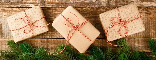 Bekijk bovenstaande bruine geschenkdoos en rood lint met tag op hout met ruimte, lange brede banner