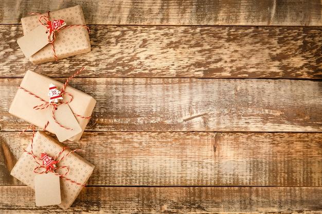 Bekijk bovenstaande geschenkdoos en rood touw met tag op hout met ruimte.