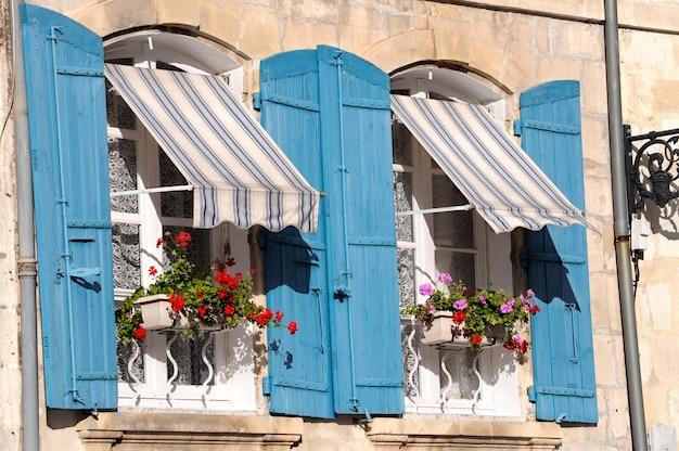 Bekijk de blauwe houten ramen met potten