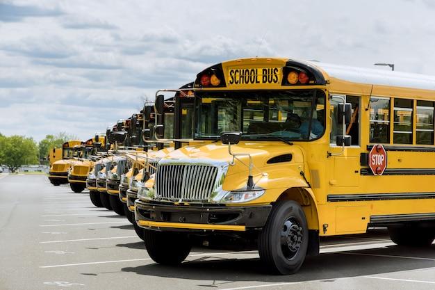 Bekijk de gele schoolbussen die bij de middelbare school geparkeerd staan