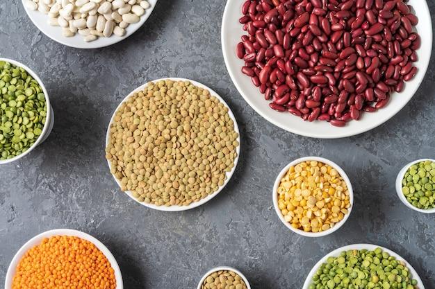 Bekijk direct hierboven van assortiment van erwten, linzen, bonen en peulvruchten over grijze achtergrond.