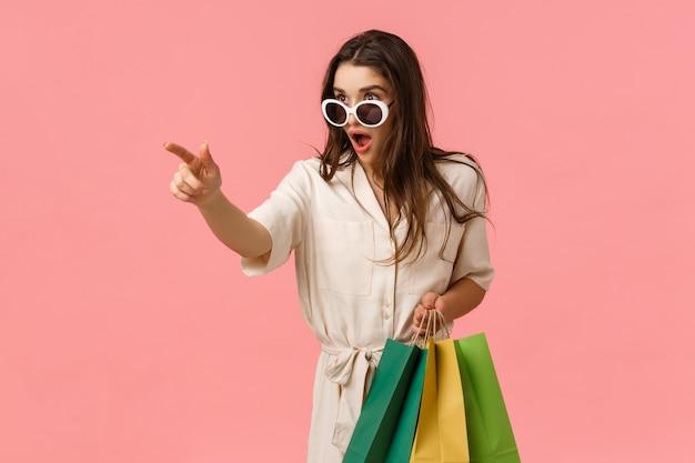 Bekijk dit, moet dit seizoen hebben. verbaasd en opgewonden jonge enthousiaste vrouwelijke shoppaholic, ziet verbazingwekkend iets aan het gangpad, houdt verzendtassen vast en wijst naar links, roze muur