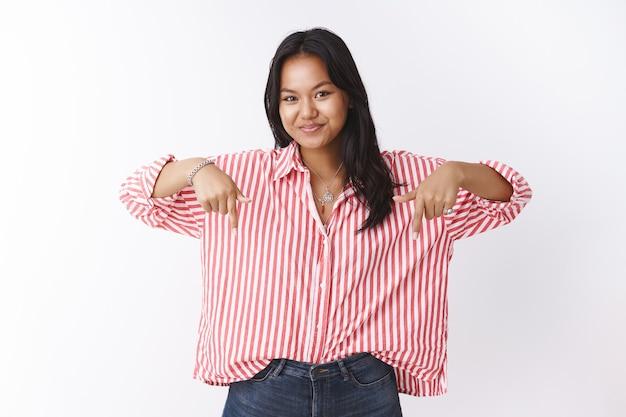 Bekijk dit nu. portret van intrigerende aantrekkelijke vietnamese vrouw in gestreepte trendy blouse die naar beneden wijst en met een grijns naar de camera staart met interessante kopieerruimte over witte muur
