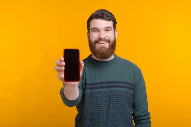 Bekijk dit online aanbod of deze advertentie. de knappe mens toont het lege scherm van zijn telefoon op gele ruimte.