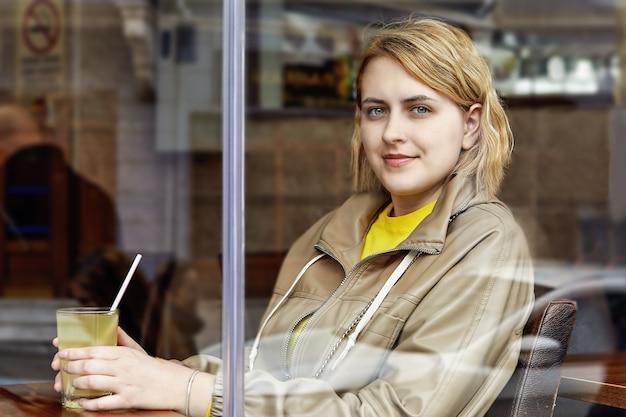 Bekijk door raam van mooie europese jonge vrouw in café met glas sap met stro in haar handen.