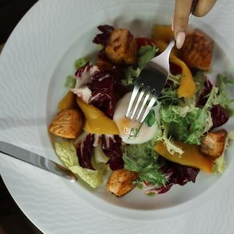 Bekijk handen met bestek en groentesalade en gepocheerd ei op een witte plaat binnenshuis op tafel. vork en mes in de handen van het meisje. gezond ontbijt