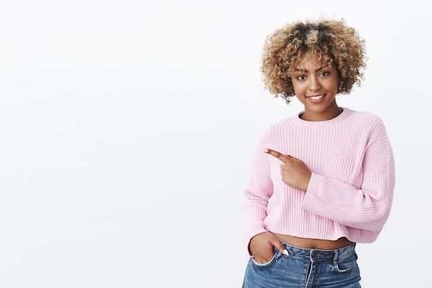 Bekijk het eens met mij. vrolijke en stijlvolle zelfverzekerde aantrekkelijke vrouw met blond afro-kapsel in warme wintertrui wijzend naar de linkerbovenhoek en glimlachend als uitnodigend of bevorderend voor kopieerruimte