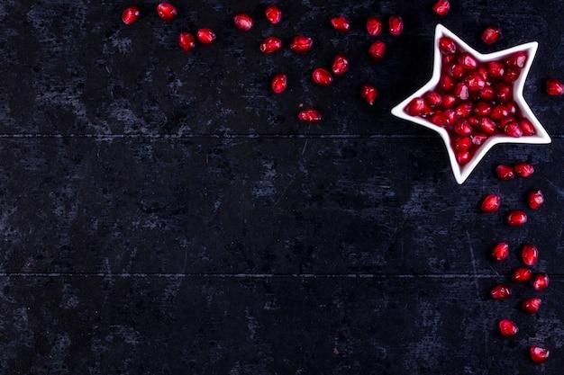 Bekijk kopie ruimte geschilde granaatappel in de vorm van een ster op een zwarte tafel
