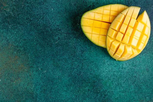 Bekijk kopie ruimte gesneden mango op een groene tafel