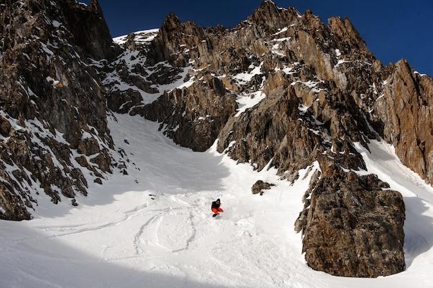 Bekijk mannelijke snowboarder in helm glijden langs de berghelling