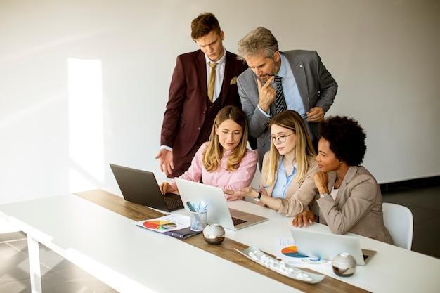 Bekijk multi-etnische groep van mensen uit het bedrijfsleven samen te werken en een nieuw project voor te bereiden op een bijeenkomst in het kantoor