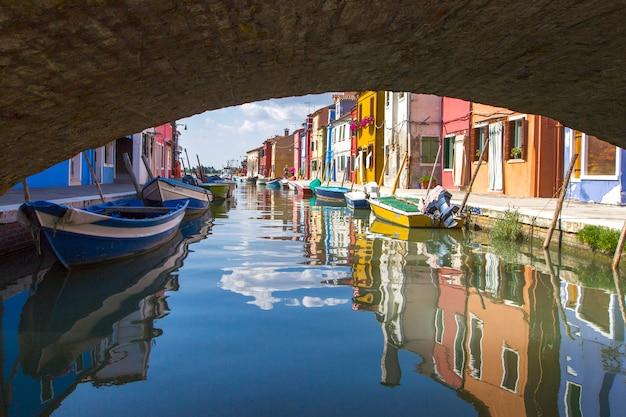 Bekijk onder brug over typische straatscène die helder geschilderde huizen en boten met bezinning langs kanaal toont bij eilanden burano in venetië, italië
