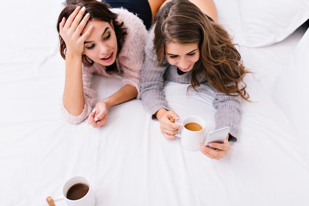 Bekijk twee jonge aantrekkelijke vrouwen die samen plezier hebben op een wit bed. goedemorgen van mooie meisjes, surfen op internet aan de telefoon, thee drinken, glimlachen.