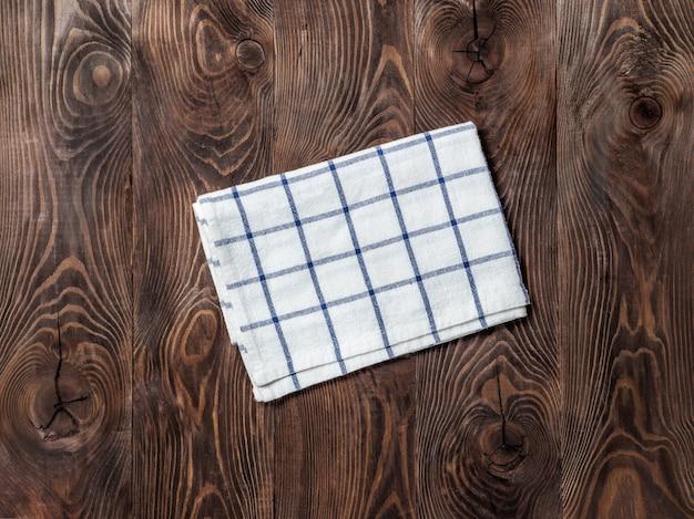 Bekijk van bovenaf op bruine houten tafel met linnen keuken handdoek of textiel servet.