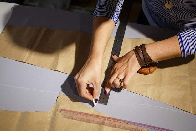 Bekijk van bovenaf op de hand van een naaister met een liniaal