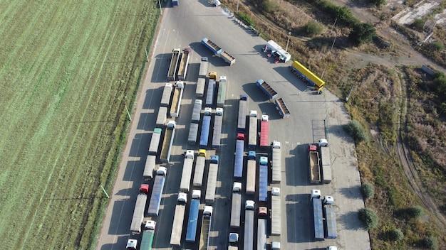 Bekijk van bovenaf op een grote rij vrachtwagens die wachten bij de haventerminal.