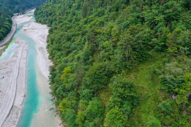 Bekijk van bovenaf, op een heldergroene bergrivier langs de snelweg tussen de bergen en het dichte groene bos op de juiste, horizontale positie