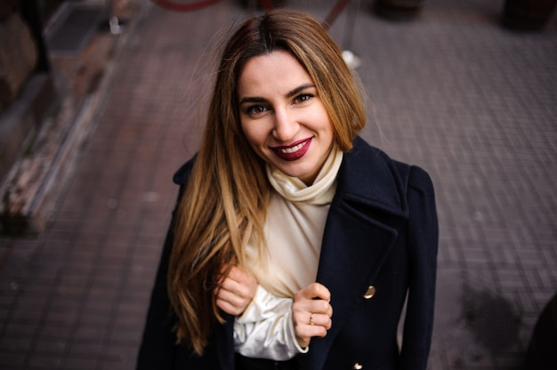 Bekijk van bovenaf op een mooie vrouw in de beige jurk en zwarte jas