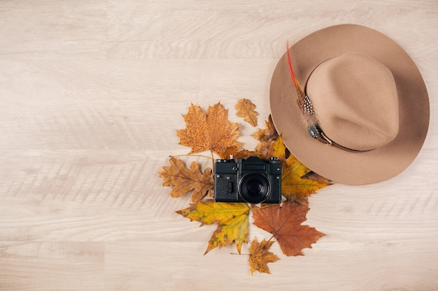 Bekijk van bovenaf op plat leggen van vrouw stijl en accessoires, herfstbladeren modetrend, vintage fotocamera, reiziger outfit