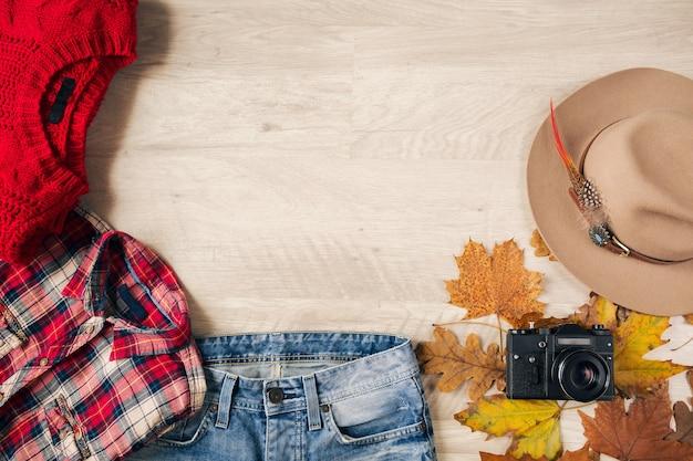 Bekijk van bovenaf op plat leggen van vrouwenstijl en accessoires, rode gebreide trui, geruit flanellen overhemd, spijkerbroek, hoed, herfstmodetrend, vintage fotocamera, reizigersoutfit