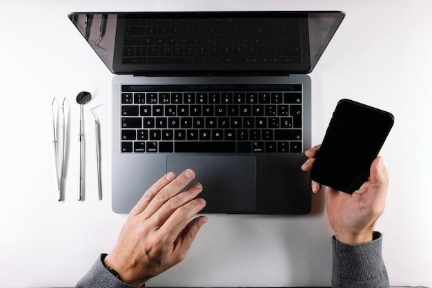 Bekijk van bovenaf van de handen van de dokter met grijze laptop en smartphone