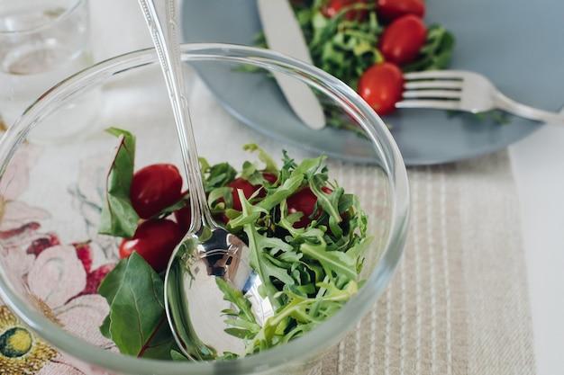 Bekijk van bovenaf van gezonde tomaten en greens liggend op grijze plaat op keuken. lekkere verse groenten, mes en vork liggend op tafel in café. concept van keuken, dieet en voeding.