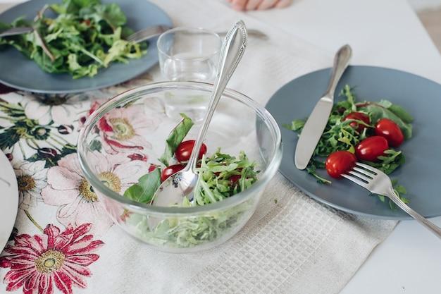Bekijk van bovenaf van gezonde tomaten en groenen liggend op een grijze plaat op keuken. lekkere verse groenten, mes en vork liggend op tafel in café. concept keuken, dieet en voeding.