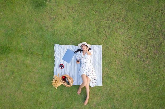Bekijk van bovenaf van jonge slanke vrouw in witte jurk tot ontspannen met laptopcomputer en koffie op groen gras achtergrond