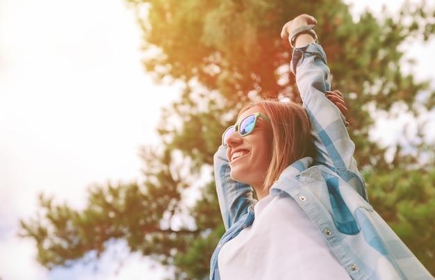 Bekijk van onderen van jonge mooie gelukkige vrouw met zonnebril en blauw geruit hemd die haar armen over een hemel en bomen opheft. vrijheid en geniet van concept.