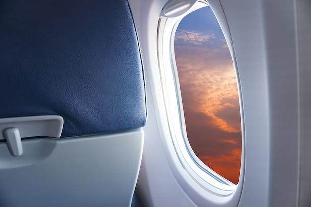 Bekijk vanuit het vliegtuigvenster de zonsondergang of de azuurblauwe lucht en de wolken vanuit het raam van het vliegtuig