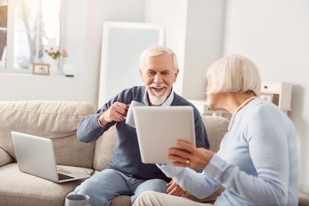 Bekijken. aangename oudere vrouw die haar man een tablet laat zien met een open nieuwsartikel erop, en de man die ernaar kijkt en koffie drinkt