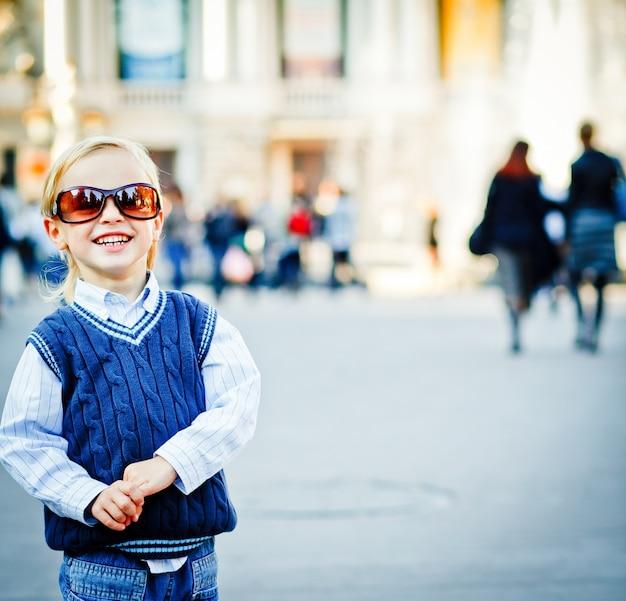 Bekijken! dat is een nieuwe ik! kleine jongen loopt in de zonnebril van de moeder