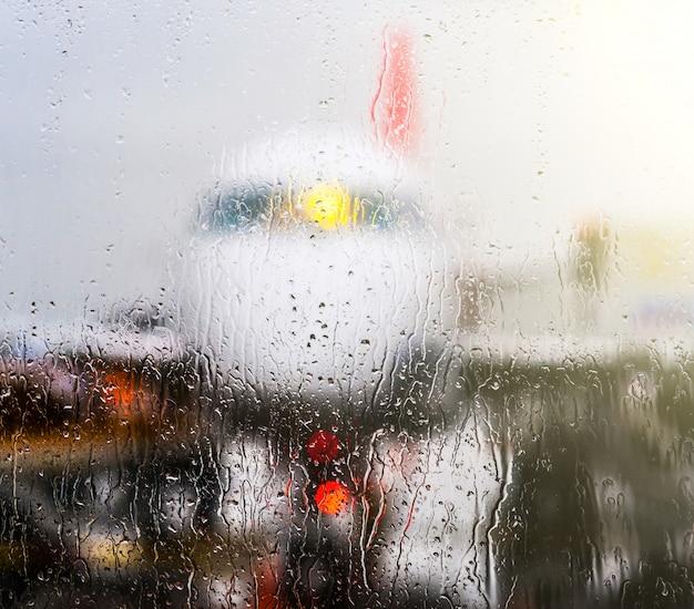 Bekijken door raam met regendruppels
