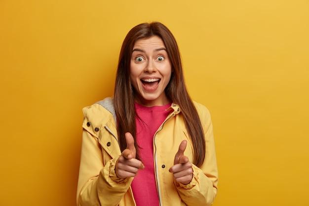 Bekijken. positieve vrolijke jonge mooie europese vrouw wijst met beide wijsvingers, zegt ja, gekleed in een informele anorak, kiest je, geïsoleerd op een gele muur, heeft een optimistische blik