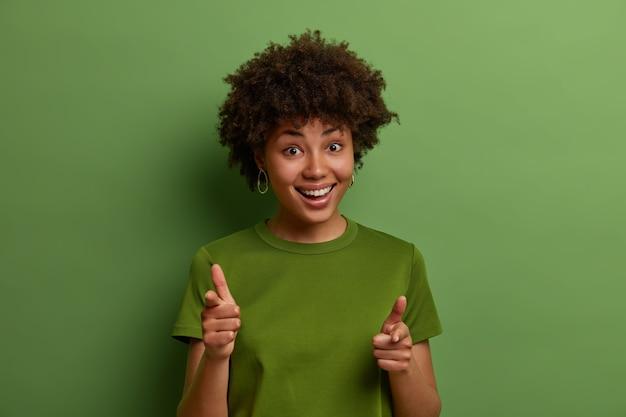 Bekijken. vriendelijke positieve jonge afro-amerikaanse vrouw wijst wijsvinger naar je, kiest een persoon en nodigt uit om lid te worden van het team, feliciteert of prijst mooie baan, geïsoleerd over groene muur