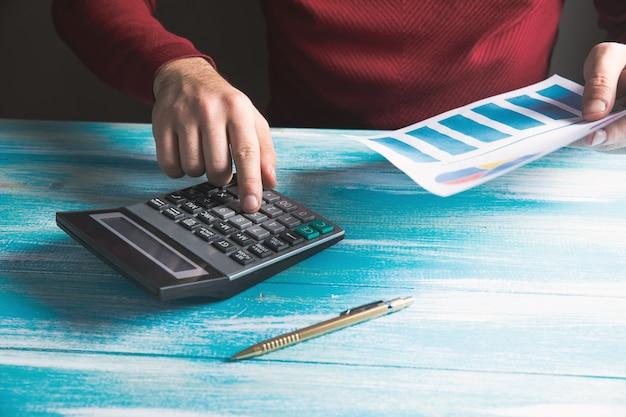Bekijkt grafieken en rekent af met een rekenmachine op tafel