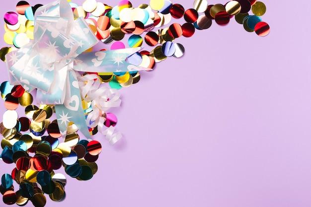 Bekleed met gekleurde confetti en een cadeau strik op een paarse achtergrond met lege advertentieruimte.
