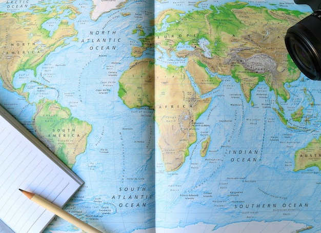 Bekleed notitieboekje met wit potlood en camera op de wereldkaart