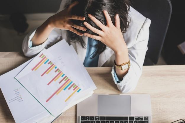 Beklemtoond of moe gebaar van vrouwelijke werknemer bij rommelig bureau.