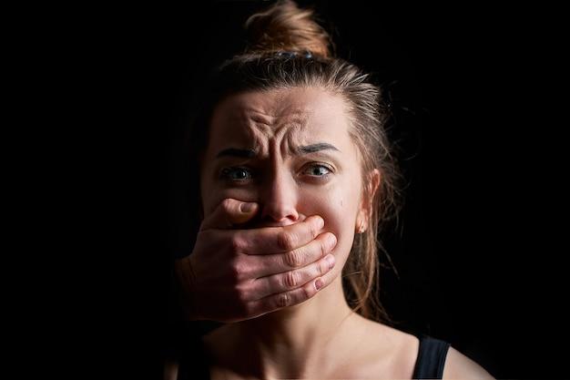 Beklemtoond ongelukkig bang huilend vrouwenslachtoffer in angst met gesloten mond op een donkere zwarte