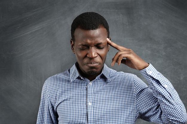 Beklemtoonde afrikaanse zakenman met een nauwgezette uitdrukking die worstelt om zich iets te herinneren, zijn ogen stijf sluitend en de vinger op zijn slaap drukt alsof hij erge hoofdpijn heeft.