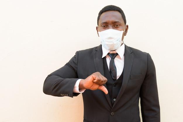 Beklemtoonde afrikaanse zakenman met masker die duimen neer tegen witte achtergrond geven