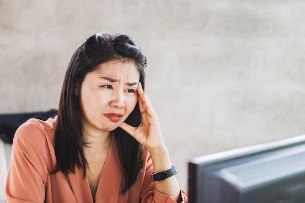 Beklemtoonde aziatische vrouwelijke arbeider die bij bureau schreeuwt
