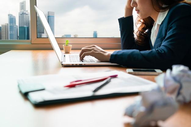 Beklemtoonde aziatische zakenvrouw die zich moe, hoofdpijn en uitgeput voelt met haar overladen financiële papieren document op het kantoor van haar financiële adviesbureau