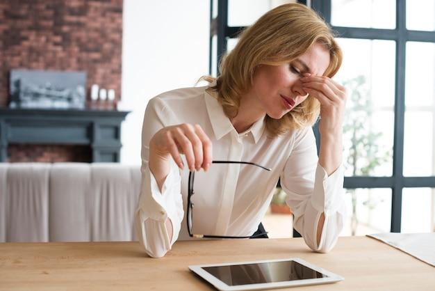 Beklemtoonde bedrijfsvrouw bij lijst met tablet