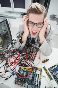 Beklemtoonde computeringenieur die aan gebroken kabels werken