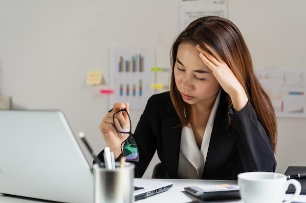 Beklemtoonde en gedeprimeerde bedrijfsvrouw die in bureau, bedrijfsfalenconcept werken