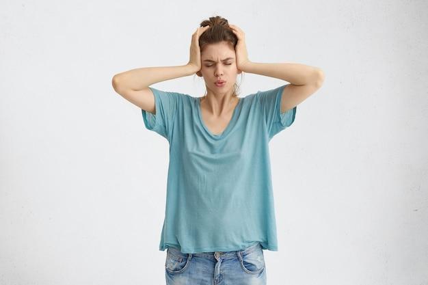 Beklemtoonde gefrustreerde jonge vrouw die oren bedekt met handen en ogen sluit vanwege lawaai