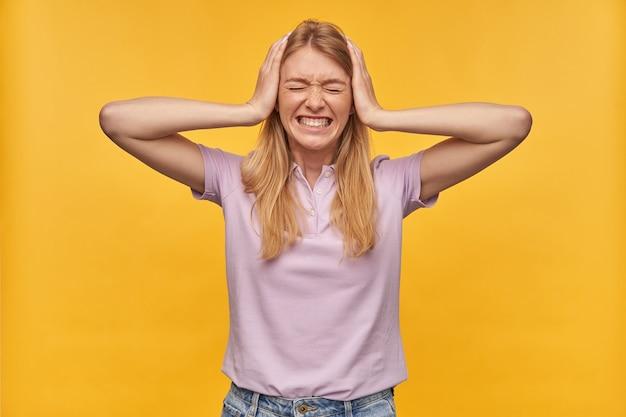 Beklemtoonde gespannen vrouw met sproeten in lavendelt-shirt houdt handen op hoofd en heeft hoofdpijn op geel